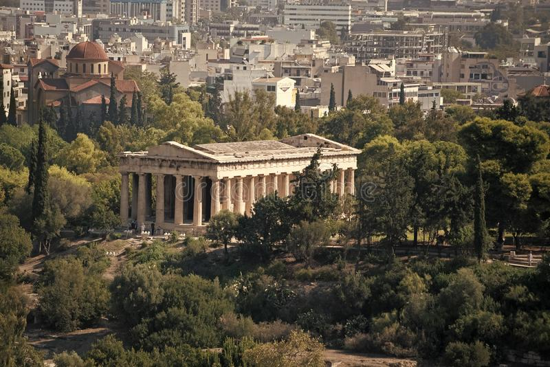 Ruinen des altgriechischen Tempels umgeben durch Park oder Waldaltbau mit Spalten mit moderner Stadt, städtischer Hintergrund stockbilder