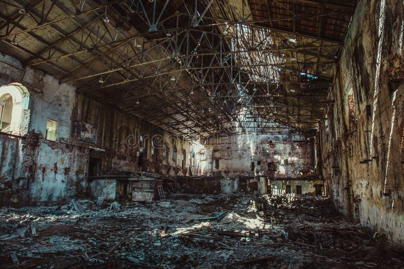 Ruinen des Industriegebäudeinnenraums nach Unfall oder Krieg oder Erdbeben, innerhalb des enormen Lagers, Pillen des Abfalls stockbilder