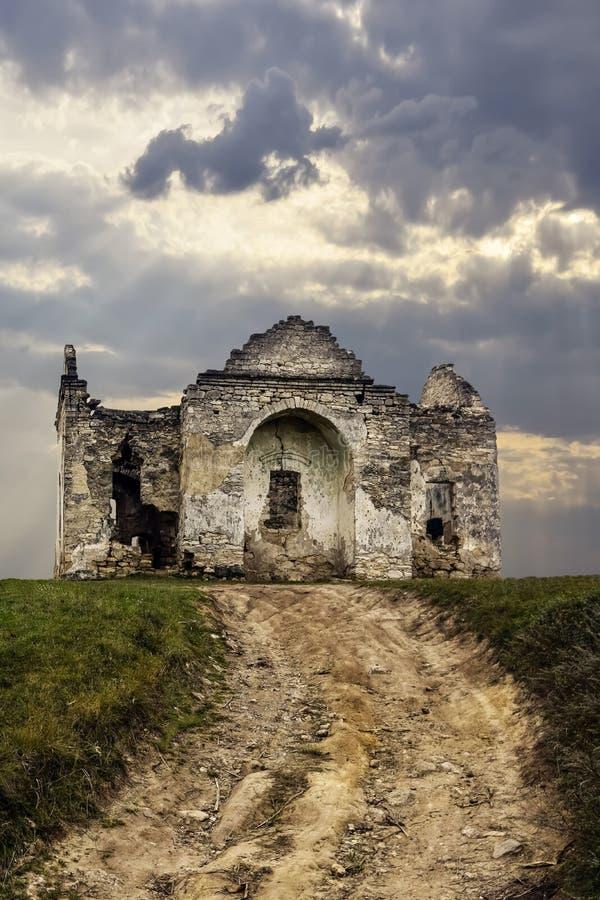 Ruiner från en gammal kristen kyrka i bakgrunden av molnig himmel Vägen fram till det gamla föråldrade templet royaltyfri foto