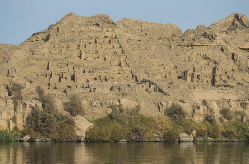 Ruines égyptiennes antiques de ville sur le flanc de montagne à Assouan Egypte photographie stock