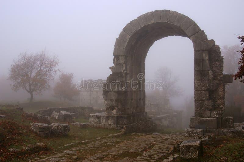 Ruines d'arc de Carsulae dans le brouillard photographie stock libre de droits