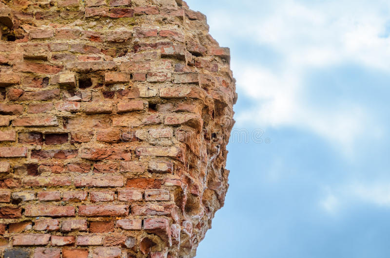 Ruines d'un mur de briques ruiné contre le ciel photo libre de droits