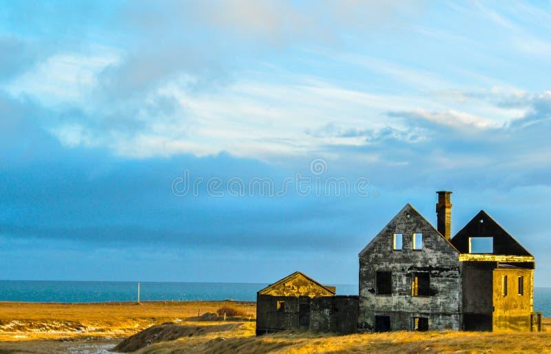 Ruines d'une maison sur une plage en Islande au coucher du soleil photo stock