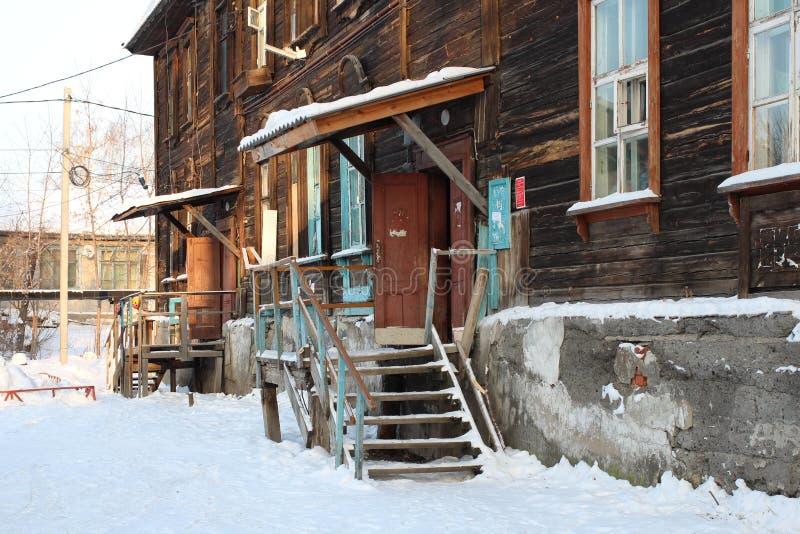 Ruines en bois de maisons d'entrée de porche vieilles abandonnées dans la cour sibérienne de village de conseils photographie stock