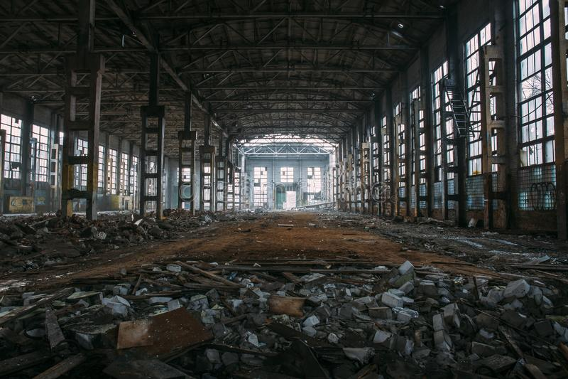 Ruines rampantes foncées de grand entrepôt ou hangar industriel abandonné démoli d'usine soviétique images stock