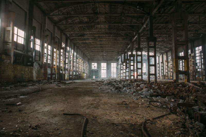 Ruines rampantes foncées de grand entrepôt ou hangar industriel abandonné démoli d'usine soviétique photographie stock