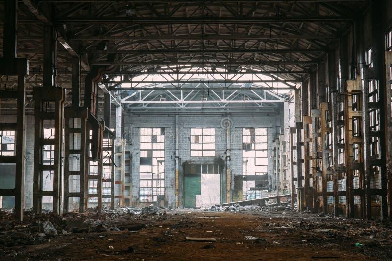 Ruines rampantes foncées de grand entrepôt ou hangar industriel abandonné démoli d'usine soviétique photos libres de droits