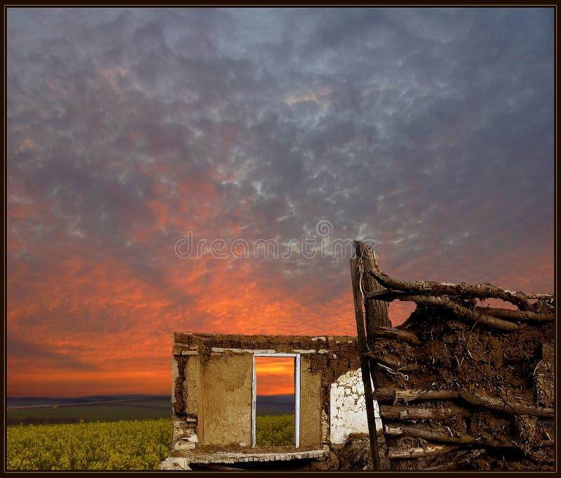 Ruiniertes Haus, drastischer, bunter Himmel und ein Blumenfeld stockfotos