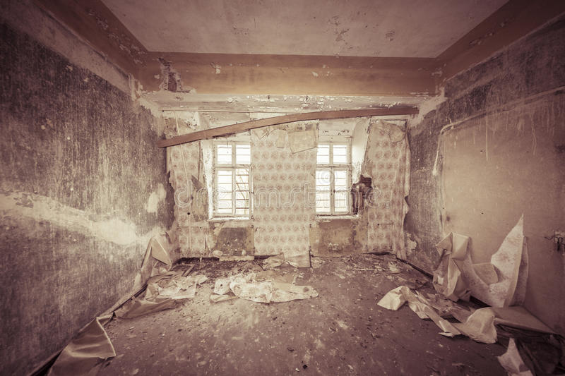 Ruinous empty room with old wallpapers. And sepia color filter stock image