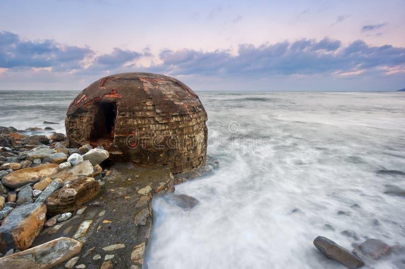 Ruins of abandoned bunker on Azkorri beach. At sunset stock photo