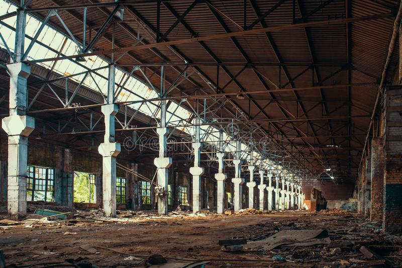 Ruins of abandoned factory or warehouse with columns, large creepy and empty industrial constriction. Toned stock photos