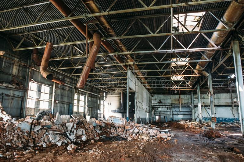 Ruins of abandoned factory or warehouse, large creepy and empty industrial constriction. Toned stock photography