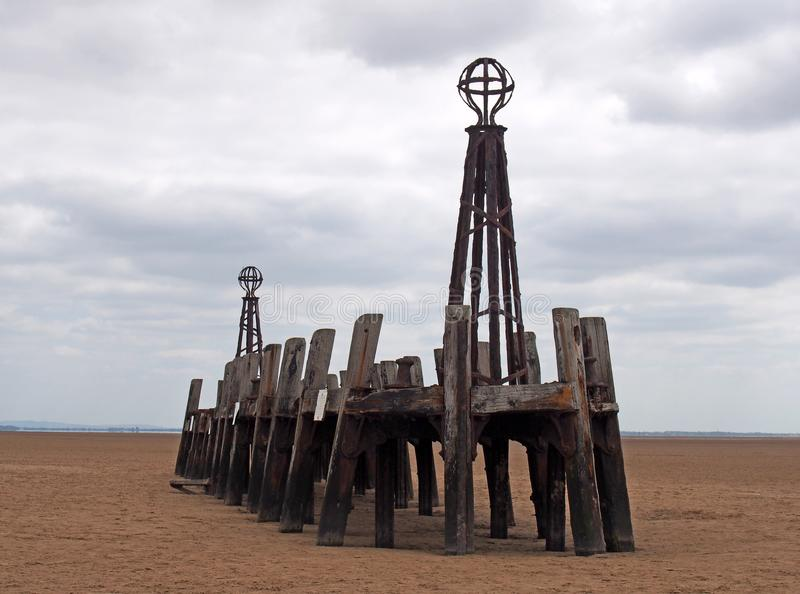 Ruins of the abandoned landing stage at saint annes pier in the ribble estuary lancashire at low tide with grey clouds. The ruins of the abandoned landing stage royalty free stock photo