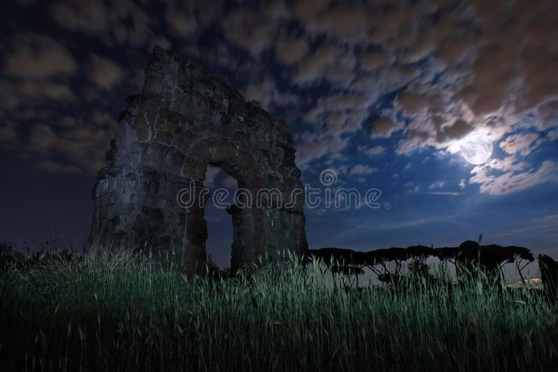 Ancient Roman aqueduct in a night scene, with the full moon stock images