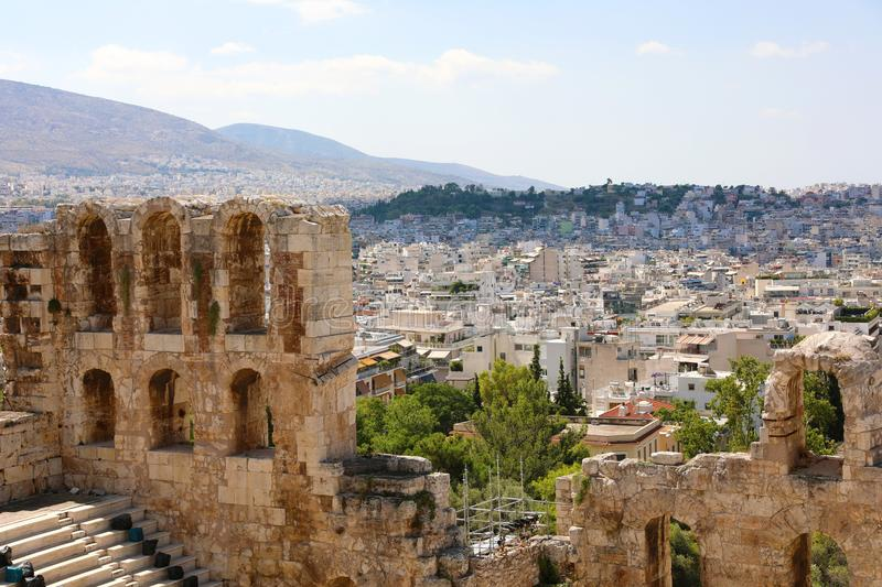 Ruins of ancient theater on the Acropolis with cityscape of Athenas. The Odeon of Herodes Atticus on the south slope royalty free stock images