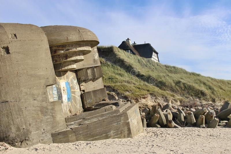 Ruins of an Atlantic Wall Bunker, and a house on the dunes. On the beach of Lokken, Denmark. Ruins of an Atlantic Wall Bunker, built by the German Armed Forces stock images