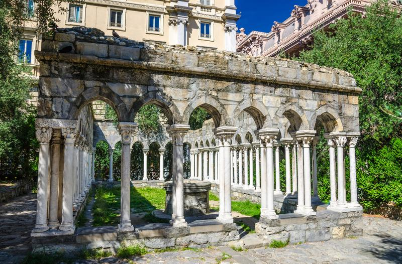 Ruins of Chiostro di Sant`Andrea monastery with columns and green plants around. In historical centre of old european city Genoa Genova, Liguria, Italy royalty free stock image