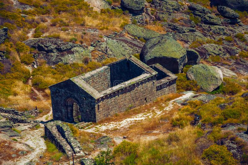 Ruins of the church of São Miguel do Castelo near Monsanto. Ruins of the church of São Miguel do Castelo on hilly landscape covered by rocks and dry bushes royalty free stock photos