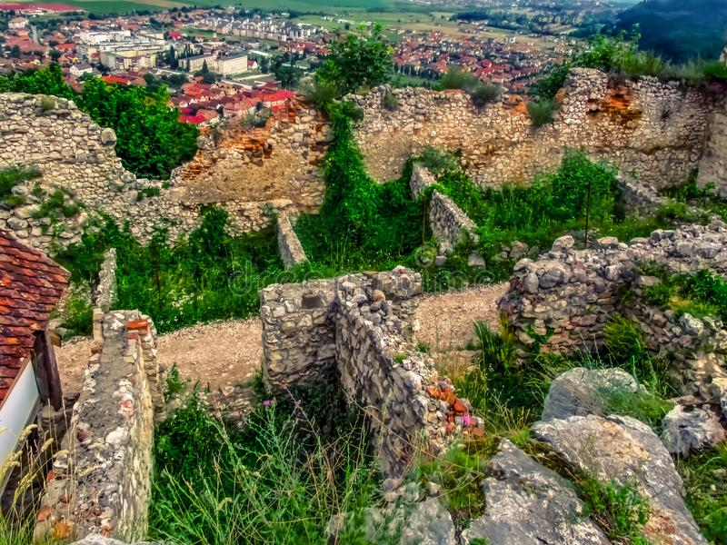 Ruins and destroyed walls of the Rasnov fortress in Romania. Archaeological site of a medieval citadel overgrown with young, lush. Grass in spring-summer day stock image