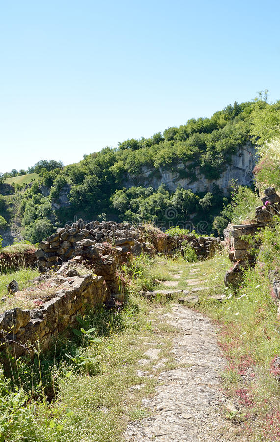 Ruins from historic monastery complex of Tsouka in Kastoria, Greece. Narrow pathway on the clif-side and ruins from historic monastery complex of Tsouka in royalty free stock photography