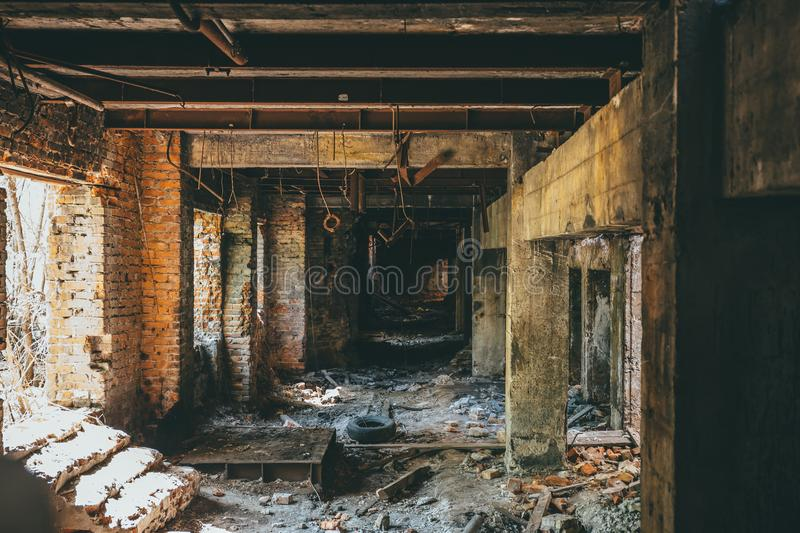 Ruins of industrial building interior after disaster or war or earthquake. Dark creepy tunnel or corridor, horror atmosphere. Vintage toned royalty free stock photography