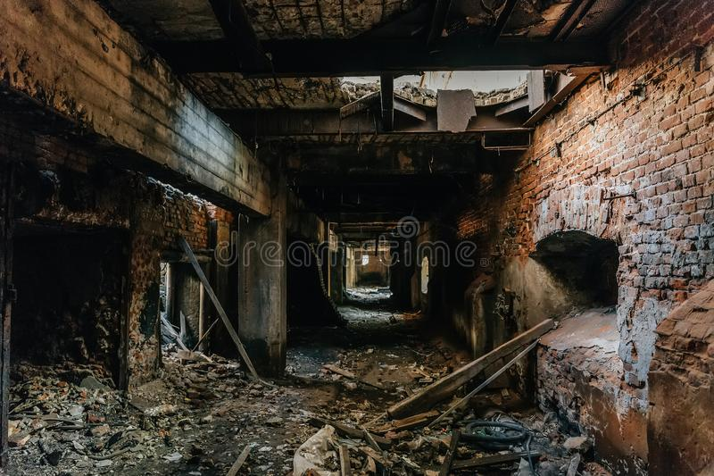 Ruins of industrial building interior after disaster or war or earthquake. Dark creepy tunnel or corridor, horror atmosphere. Vintage toned royalty free stock image