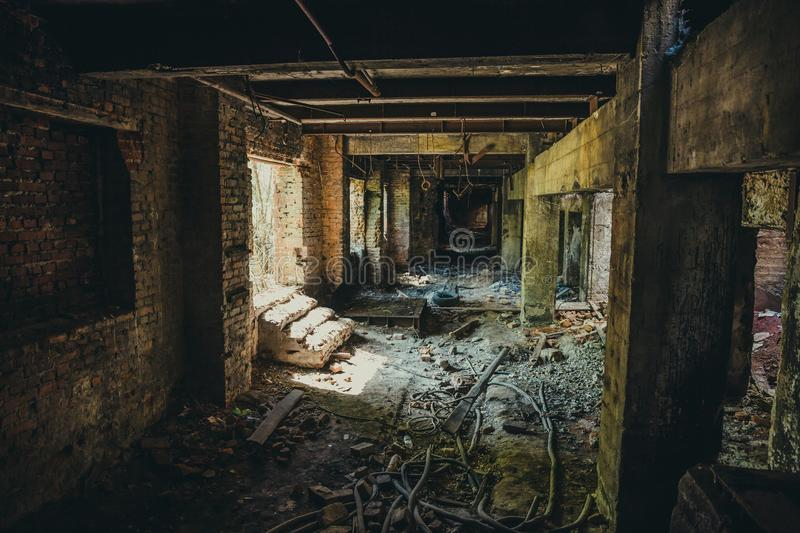 Ruins of industrial building interior after disaster or war or earthquake. Dark creepy tunnel or corridor, horror atmosphere. Vintage toned stock photography