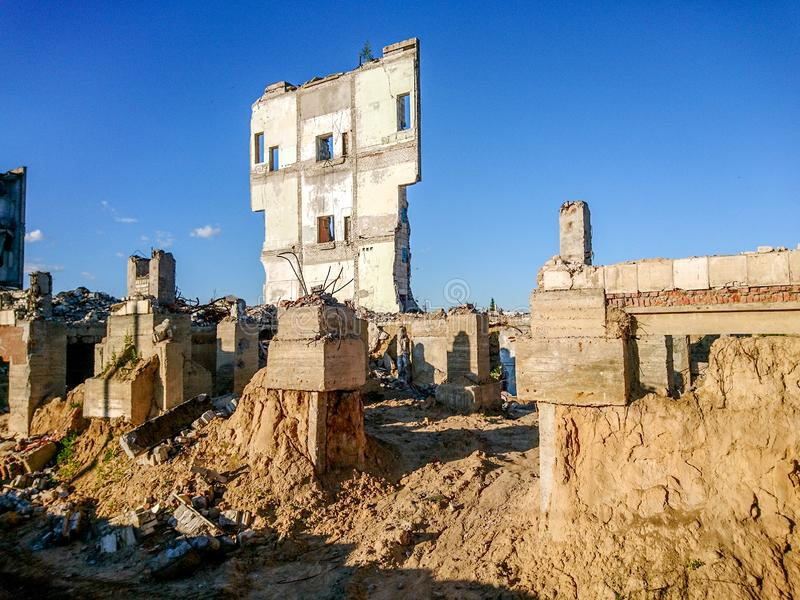 The ruins of a large destroyed building, pieces of stone, concrete, clay and metal against the blue clear sky.  royalty free stock photos