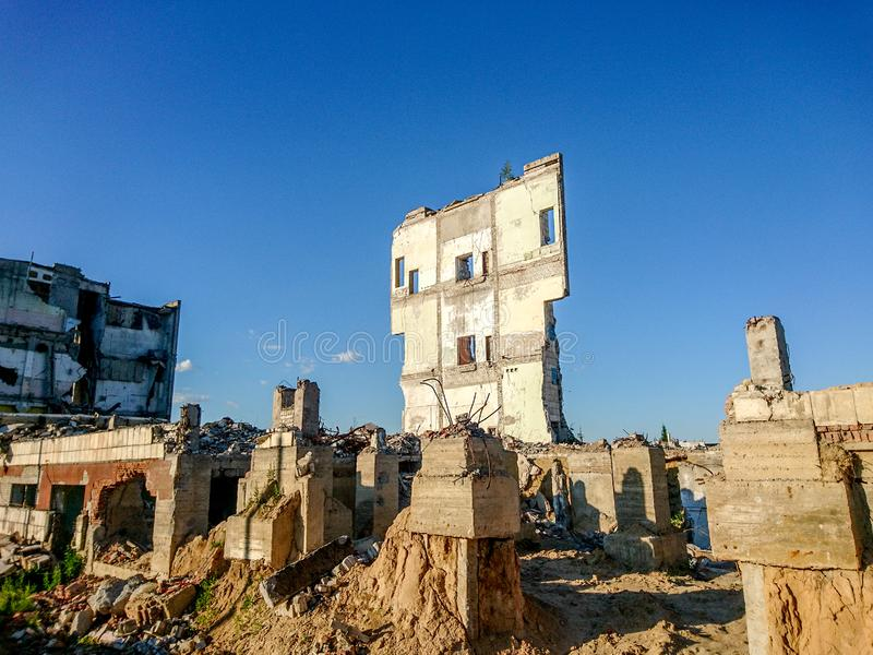 The ruins of a large destroyed building, pieces of stone, concrete, clay and metal against the blue clear sky.  stock image