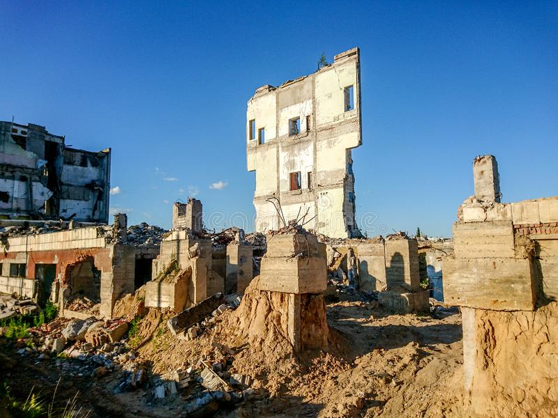 The ruins of a large destroyed building, pieces of stone, concrete, clay and metal against the blue clear sky.  royalty free stock photography