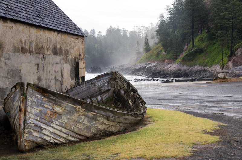 Ruins, Norfolk Island. An old lighter (small boat used to ferry cargo) against a stone building from the convict settlement in the world heritage stock photography