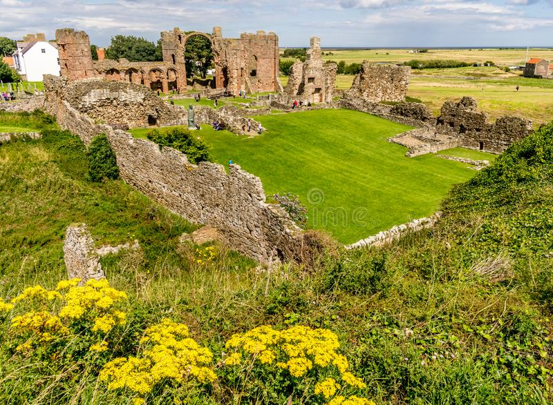 Ruins of an old building with a church spire in the background. The ruins of a monastery. holy island. sandstone bricks. an arch or arches. a church tower or royalty free stock image