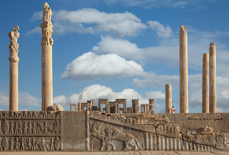 Ruins of Persepolis UNESCO World Heritage Site Against Cloudy Blue Sky in Shiraz City of Iran. Ruins of Apadana and Tachara Palace behind stairway with bas stock photography