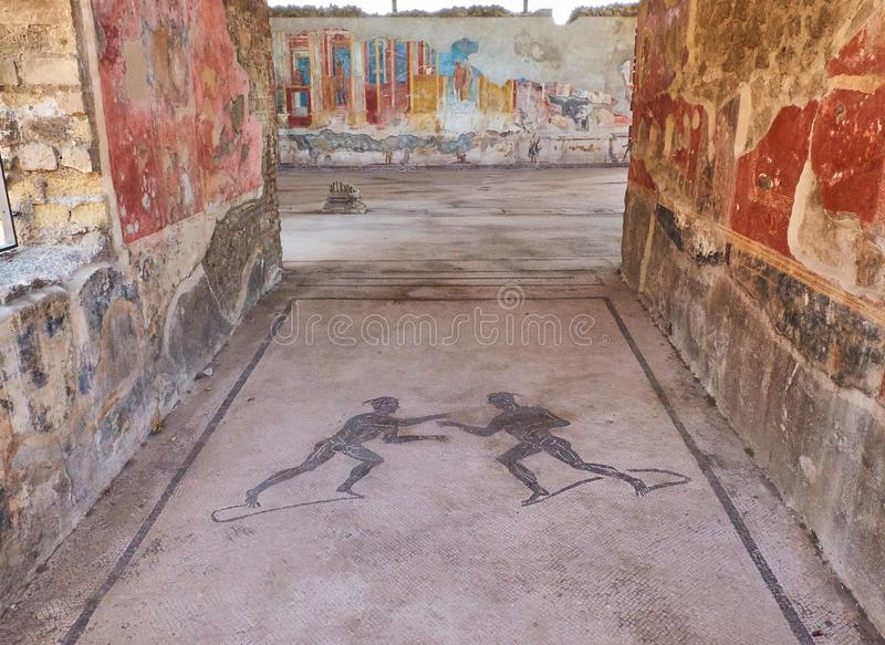 Ruins of Pompeii, ancient Roman city. Pompei, Campania. Italy. Mosaics at entrance of archaeological remains of Palestra Palestri Dei Luvenes in Ruins of stock image