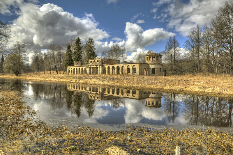 Ruins poultry house in the Park Menagerie. Gatchina. Russia. Gatchina, Russia - April 24, 2016: Stone dilapidated building with two corner towers, standing on stock images