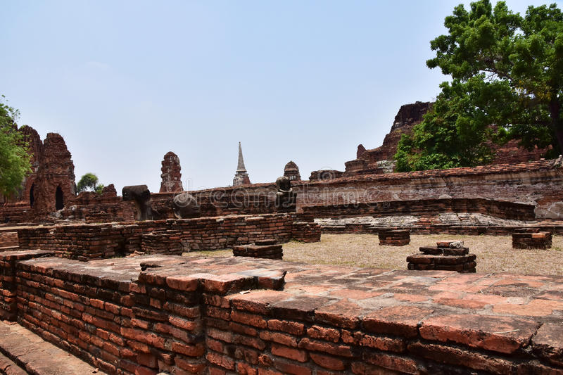 Ruins of stupa and statue of Buddha in Wat Mahathat, the ancient Thai temple in Ayutthaya Historical Park. royalty free stock images