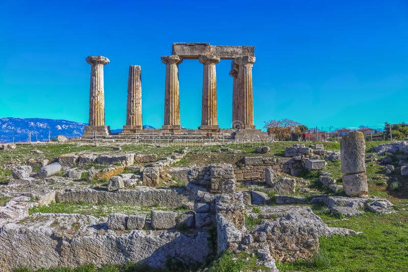 Ruins of Temple of Apollo in Corinth Greece standing up on a hill with remenants of rock walls scattered about under a bright sun stock photo