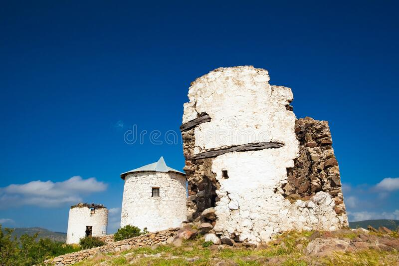 Ruins of three white windmills against dark blue sky near Bodrum, Turkey. Toy windmills are most popular souvenirs in Bodrum royalty free stock photo