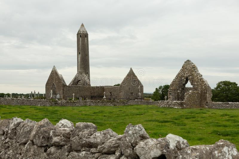 Ruins of a tower and church. Ruins of a church and a tower on the 11th century monastic site of Kilmacduagh, Ireland stock photo