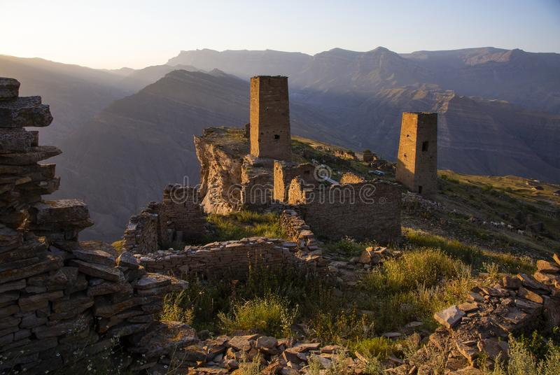 The remains of the aul of the ghost Goor in Dagestan in the evening. Ruins and towers of the aul ghost Goor in Dagestan in the evening light royalty free stock photo