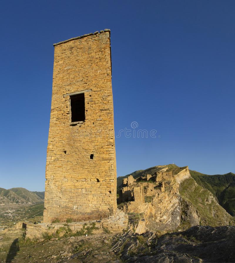 The remains of the aul of the ghost Goor in Dagestan in the evening. Ruins and towers of the aul ghost Goor in Dagestan in the evening light stock images