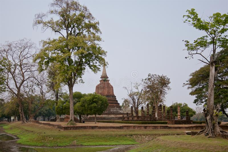 Ruins of unique temples in famous Sukhothai Historical Park. A UNESCO World Heritage Site, Foggy spring day in the ancient 13th and 14th centuries capital of stock photo