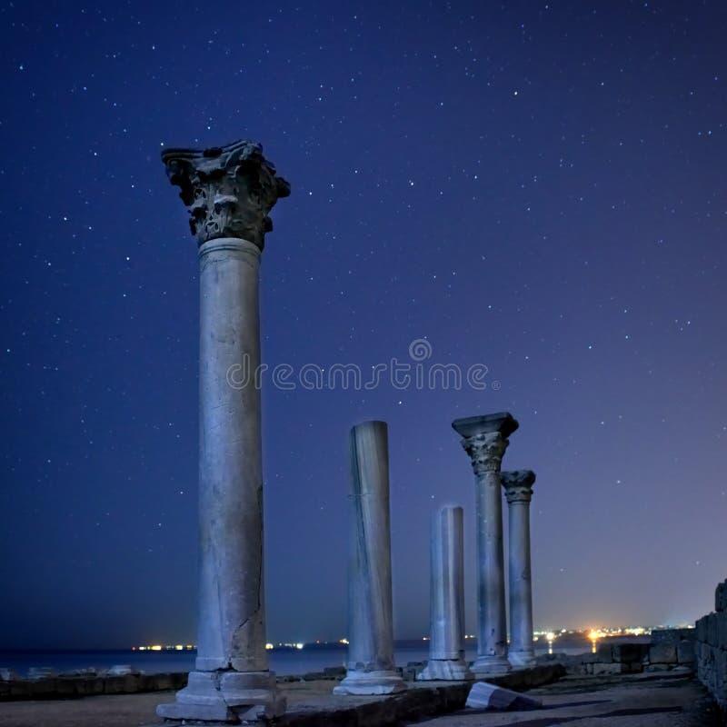 Ruiny antycznego miasta kolumny pod nocnym niebem zdjęcia royalty free