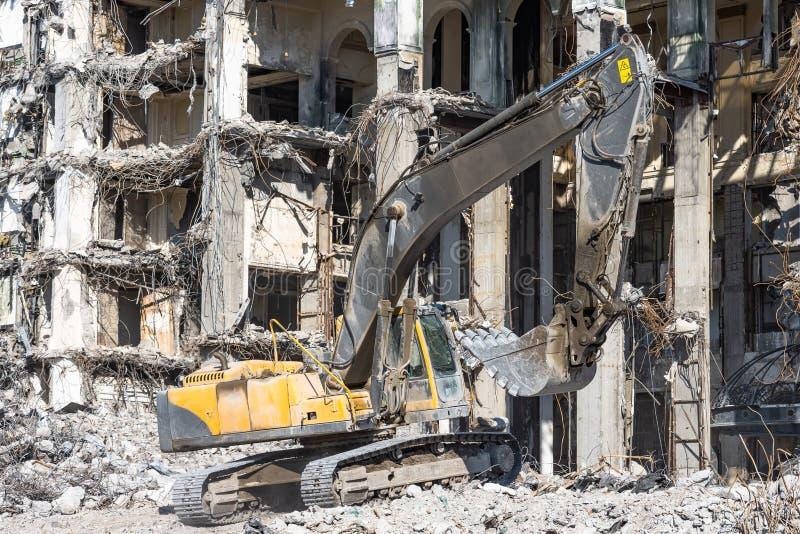 Ruiny wyburzający zawalony budynek, stosy kamienie i pyłu ekskawatoru pracy z wiadrem, obrazy royalty free