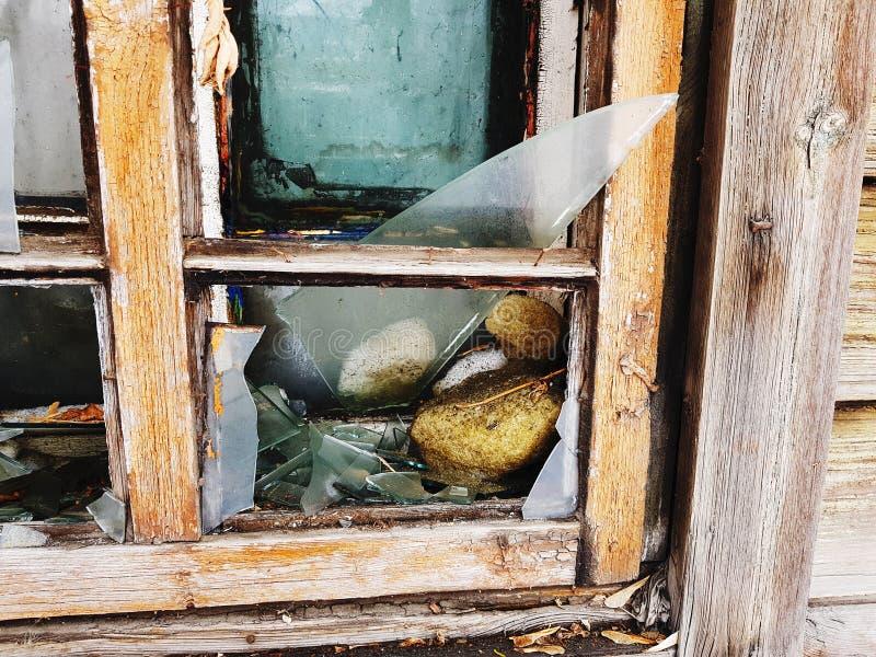 Ruit met een gebroken venster in het oude huis op de achtergrond van sneeuw in de winter stock afbeeldingen
