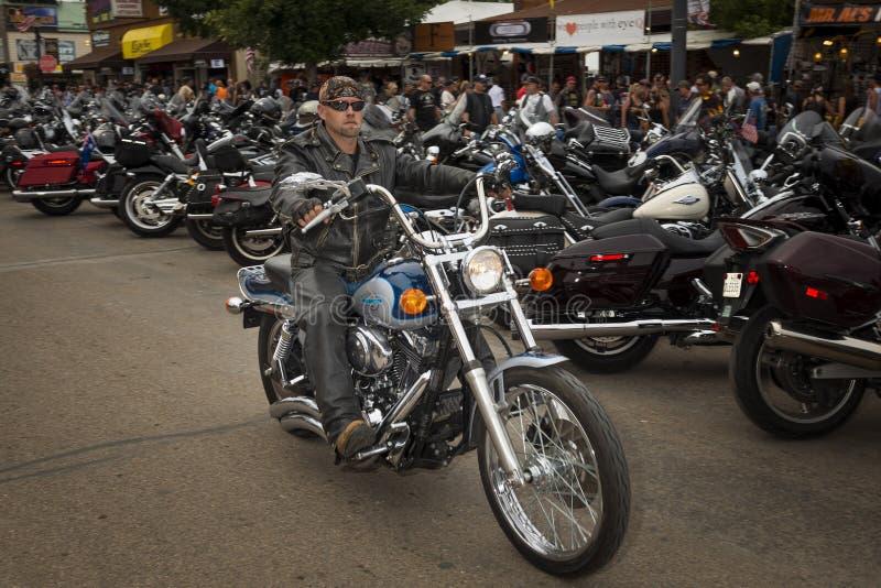 Ruiter in de hoofdstraat van de stad van Sturgis, in Zuid-Dakota, de V.S., tijdens de jaarlijkse Sturgis-Motorfietsverzameling stock afbeelding