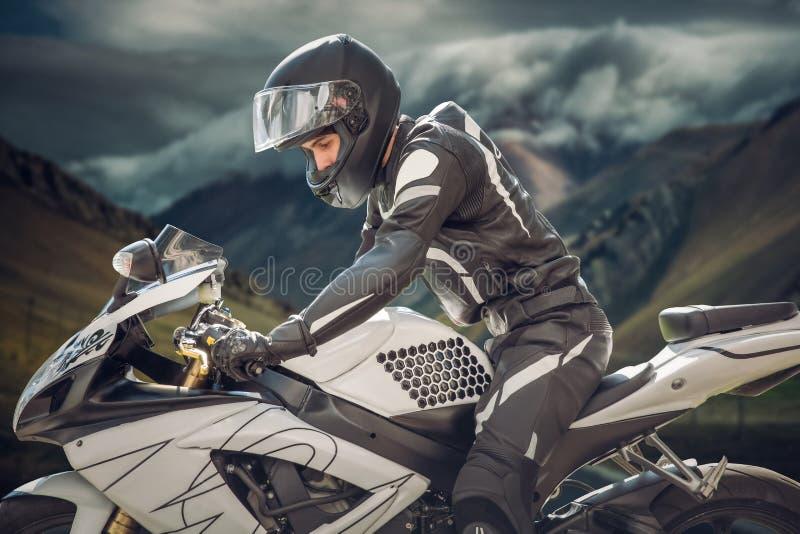 Ruiter op een motorfiets met Belangrijkste Berg als achtergrond bergen van een wolk stock foto