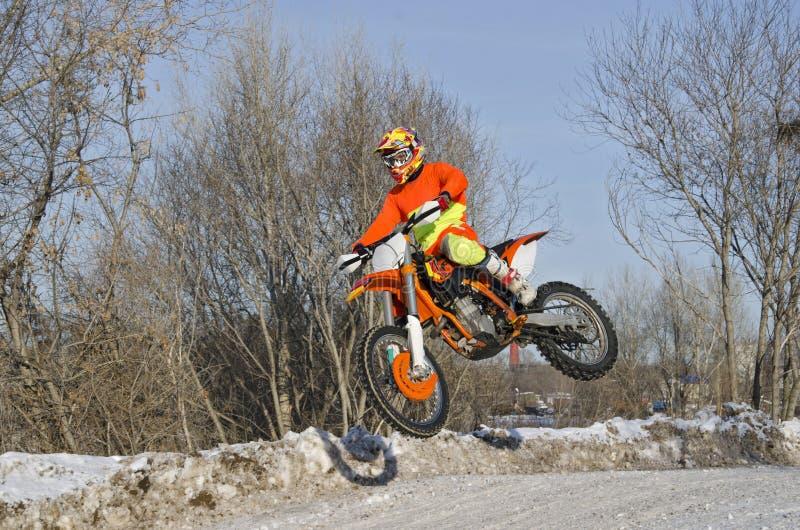 Ruiter op fiets voor MX vliegen over heuvel op sneeuwweg royalty-vrije stock afbeelding