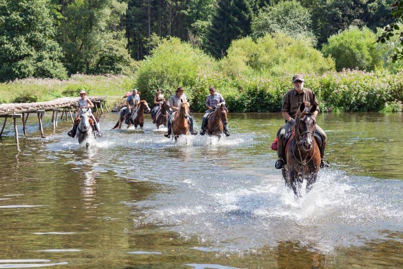 Ruiters en paarden die de rivier Semois kruisen dichtbij Laferet, België stock afbeeldingen