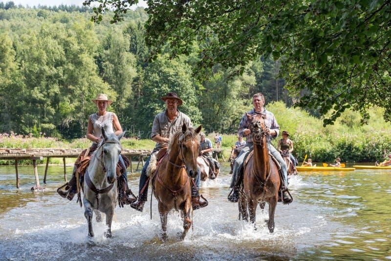 Ruiters en paarden die de rivier Semois kruisen dichtbij Laferet, België royalty-vrije stock foto's